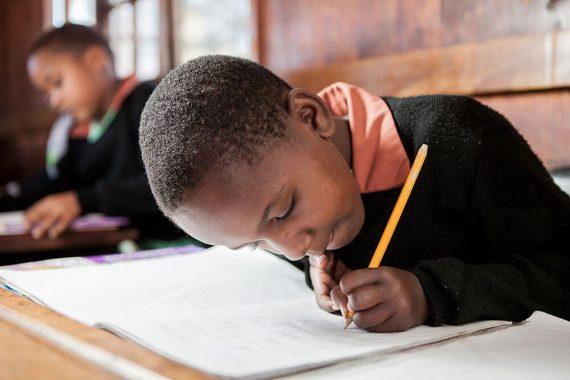 Boy writing in book